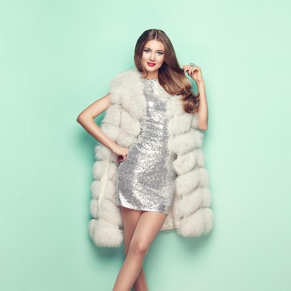 Retrato de moda de una joven ucraniana en un abrigo de piel blanco de pie todavía