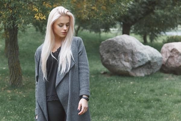 Joven mujer ucraniana de pelo rubio en un abrigo gris con pulsera inteligente de pie al aire libre