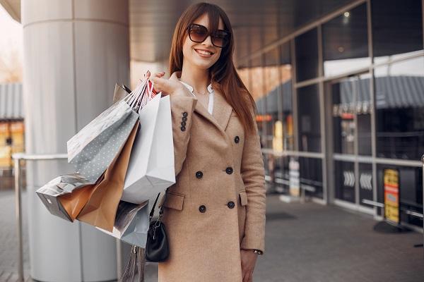 Sonriente joven mujer ucraniana con bolsas de compras de pie en el centro de la ciudad.